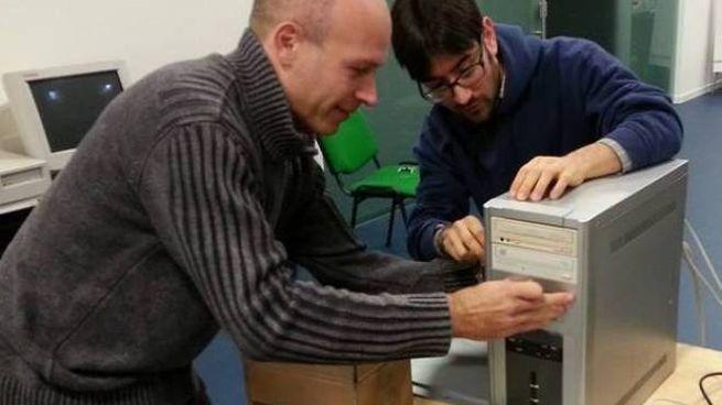BRAVISSIMI Alcuni volontari dell'associazione Gulli mentre sistemano un computer