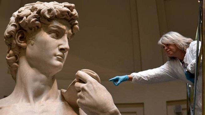 "An Italian restorer from the ""friends of Florence association"" works on cleaning Michelangelo's David, one of the world's most famous statues, on February 29, 2016 at the Galleria del'Accademia in Florence, where the statue has been kept since 1873. / AFP / ALBERTO PIZZOLI"