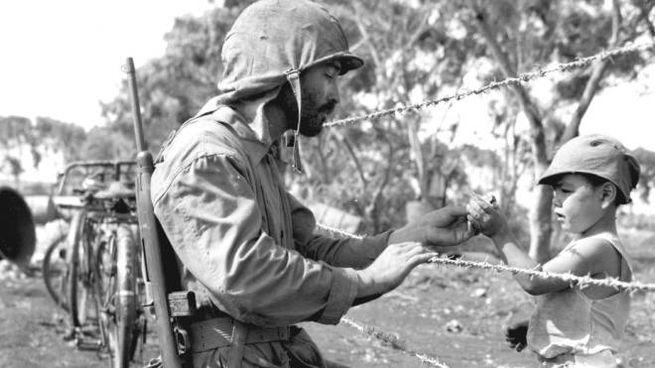 Un soldato regala una caramella a un bambino