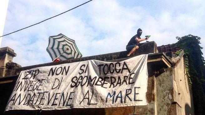 Un manifestante sul tetto dell'ex asilo occupato
