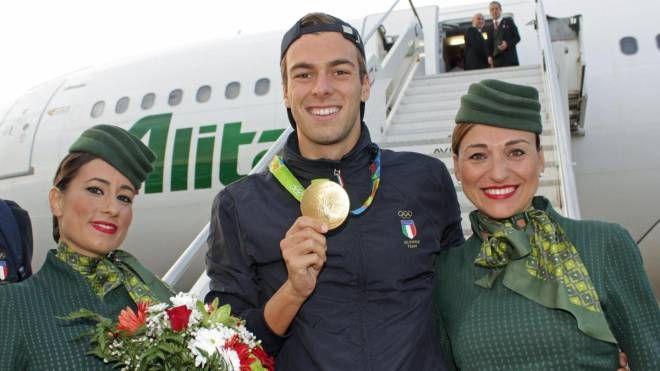 Gregorio Paltrinieri atterra a Roma e posa con le hostess per una foto ricordo (Ansa)