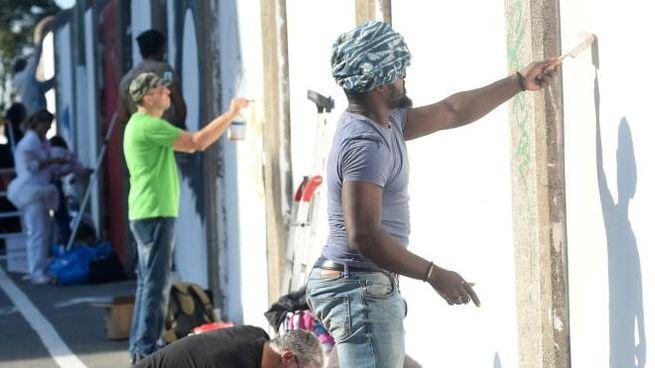 I volontari imbiancano il ponte per permettere poi agli artisti di disegnarci sopra