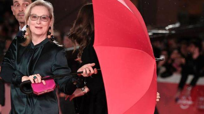 Meryl Streep sul red carpet con un gigantesco ombrello rosso (Afp)
