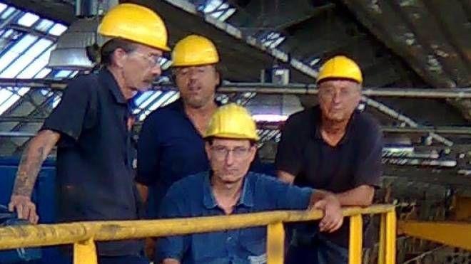 Da sinistra, Massimo Merlo e gli altri tre operai  sul carroponte a dieci metri di altezza all'interno della fabbrica