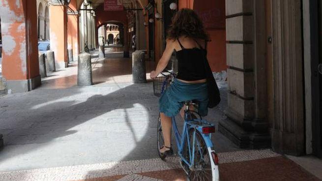 Una ciclista sotto il portico di Strada Maggiore in una foto d'archivio