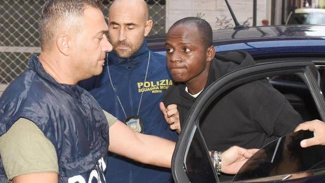 Guerlin Butungu con gli agenti della squadra mobile (foto Ansa)
