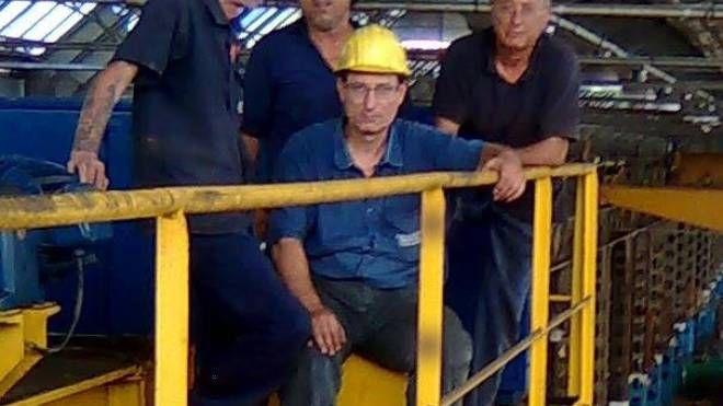 Da sinistra Massimo Merlo e gli altri operai sul carroponte della Innse (NewPress)