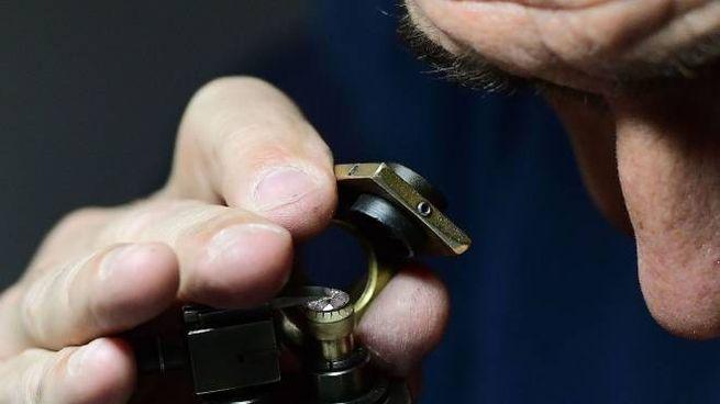 Un esperto di preziosi controlla al microscopio il valore di un diamante