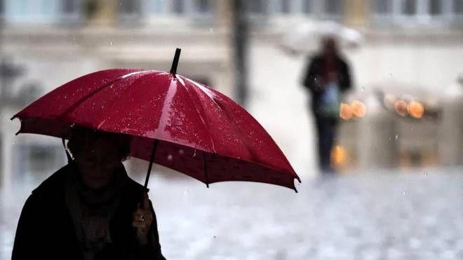 Una persona si ripara con l'ombrello (Ansa)