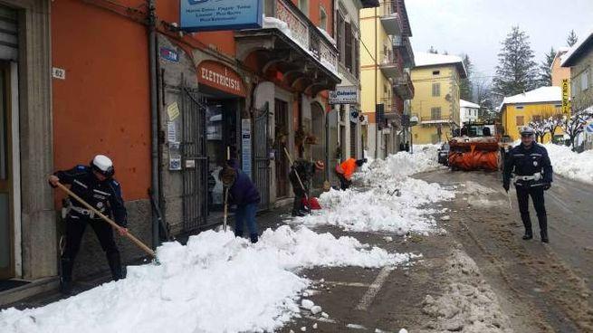 Vigili, operai e commercianti spalano la neve a Pieve (Foto Milena Vanoni)