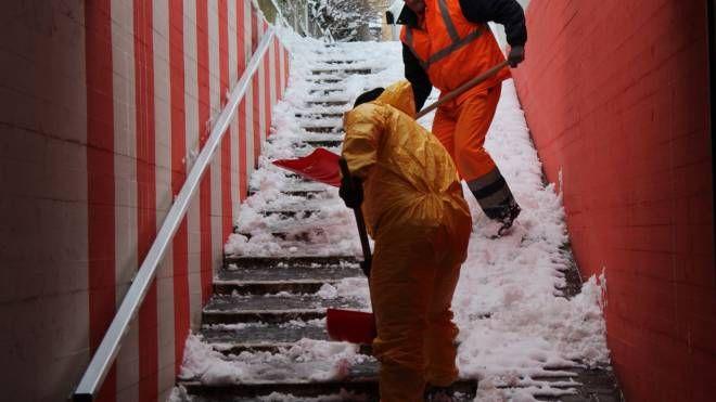 Operai al lavori per liberare i gradini di un sottopasso di Marotta dalla neve