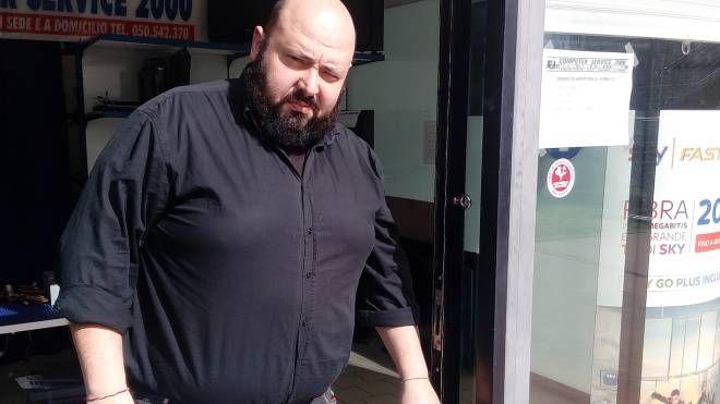 Davide De Minicis mostra i segni di effrazione alla porta del suo negozio
