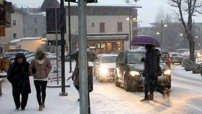 Pedoni e auto a Bormio sotto una fitta nevicata