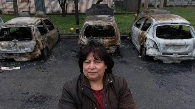 Maria Palomares del comitato No racket non abusivismo. Sullo sfondo le auto incendiate