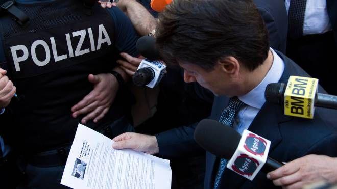 Il presidente del Consiglio Giuseppe Conte legge il volantino stampato e distribuito dai lavoratori della FedEx