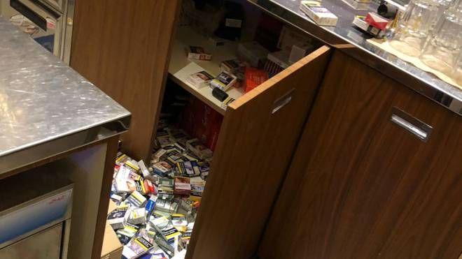 Il caos lasciato dai ladri dopo l'incursione da Gigi's bar. A destra, una dipendente osserva gli scaffali vuoti