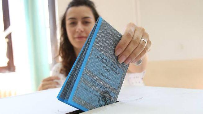 Una votante imbuca la scheda nell'urna