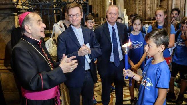 L'arcivescovo Mario Delpini consegna la fiamma olimpica ai ragazzi
