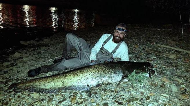 Il dj Remo Giugni con il pesce siluro pescato in Arno