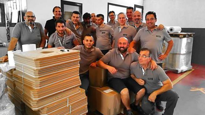 Alcuni dipendenti dell'Italnastri in azienda: sorridono perché l'occupazione per loro non è sfumata