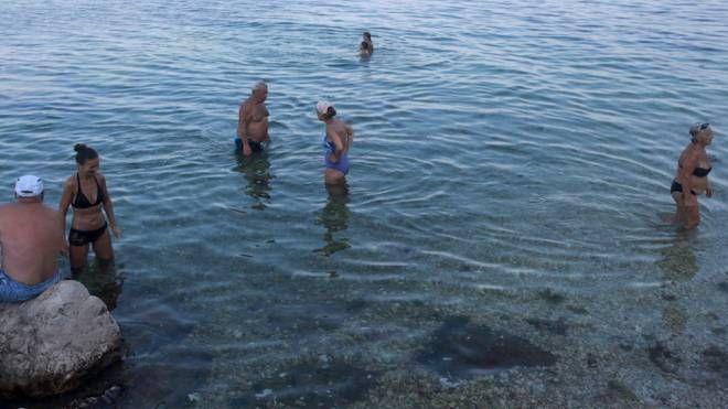 Bagnanti e turisti in acqua nonostante il pericolo