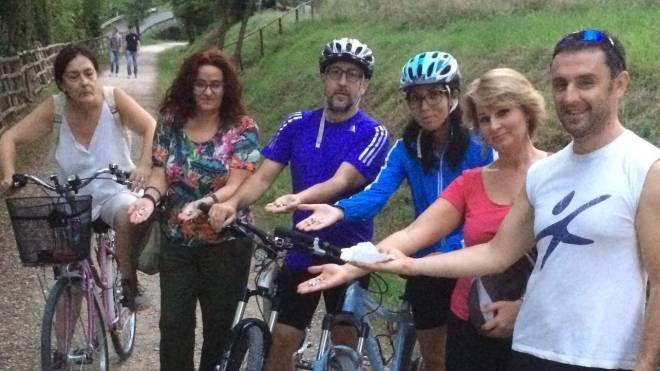 Un gruppo di ciclisti mostra le puntine  di ferro trovate lungo la pista ciclo-pedonale