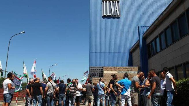 Ilva, un gruppo di lavoratori davanti allo stabilimento di Taranto (Ansa)