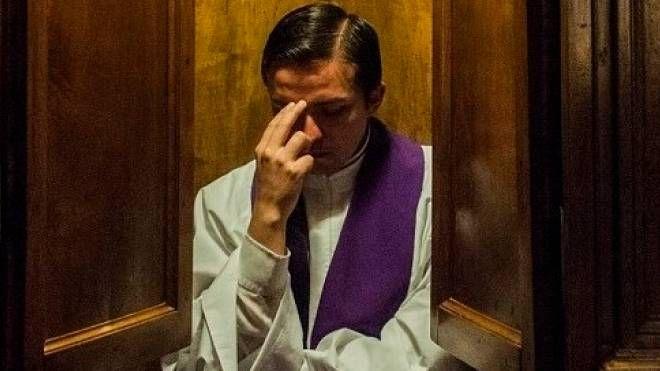 Un prete in un confessionale