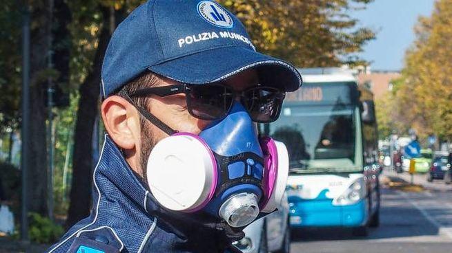 Un vigile urbano mentre dirige il traffico con la maschera antismog: nella giornata di ieri non ci sono state multe per il mancato rispetto dell'ordinanza