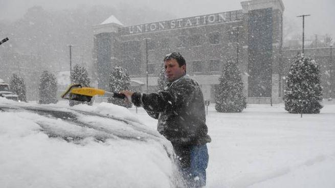 Un uomo impegnato a liberate la sua auto dalla neve (Ansa)