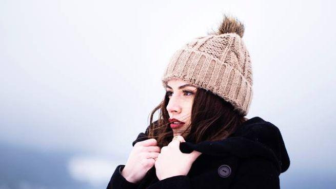 Ragazza si copre dal freddo (Foto d'archivio)