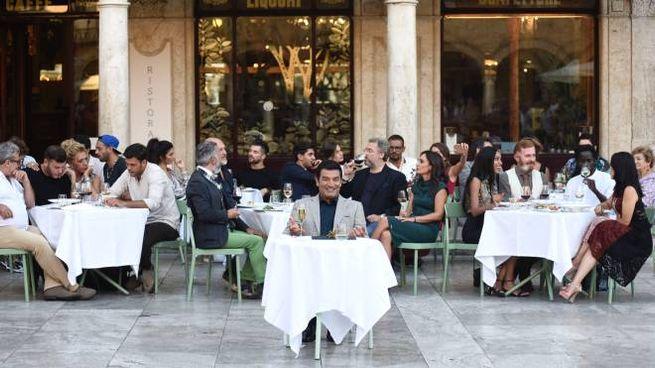 Max Giusti seduto ai tavolini del Caffè Meletti in piazza del Popolo