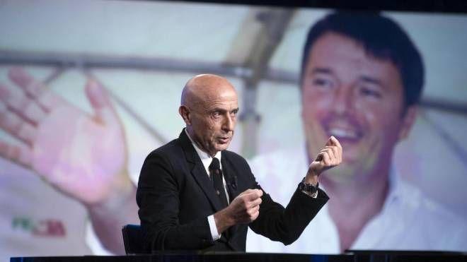 Marco Minniti, alle sue spalle una foto di Matteo Renzi (Ansa)