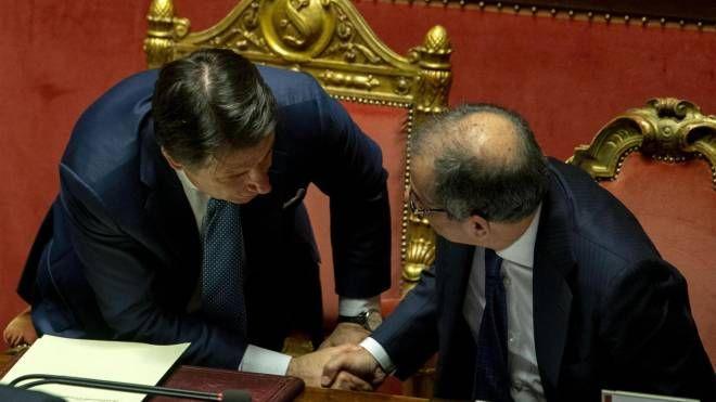 Stretta di mano fra il premier Conte e il ministro dell'Economia Tria (Ansa)