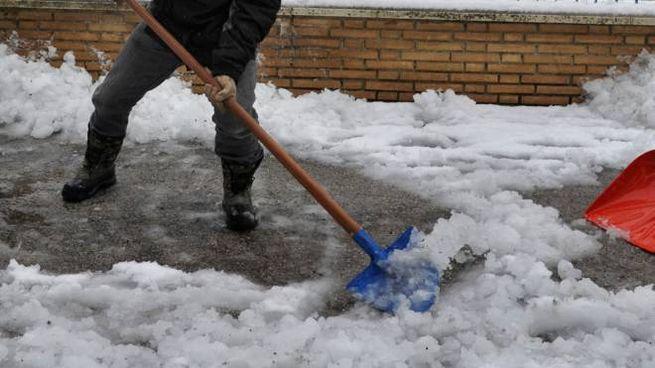 Un uomo spala la neve davanti  alla scuola di Sforzacosta