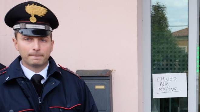 Un carabiniere di fianco al cartello 'chiuso per rapina'