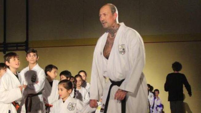 Mauro Genocchio porta per mano una piccola allieva all'inizio del suo percorso nel karate