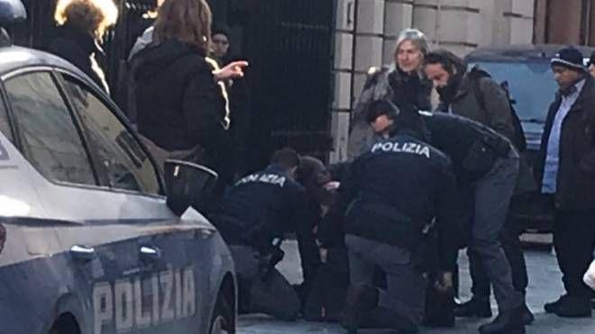 Nella foto il momento in cui il 31enne moldavo viene consegnato alla polizia di Stato che lo arresta