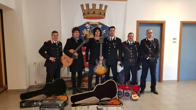 I Negrita con i carabinieri ricevono le chitarre rubate