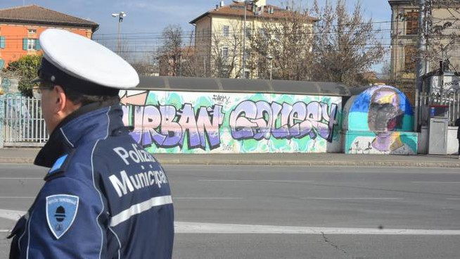 La polizia e sullo sfondo il murales imbrattato