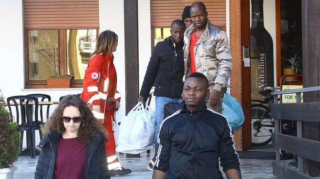 Alcuni richiedenti asilo, accompagnati da un'assistente, mentre lasciano l'ex hotel Bellevue