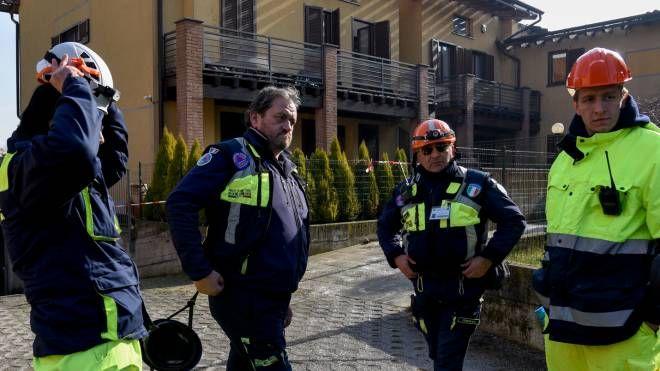 Gli uomini della Protezione civile fuori dalle abitazioni interessate dall'incendio