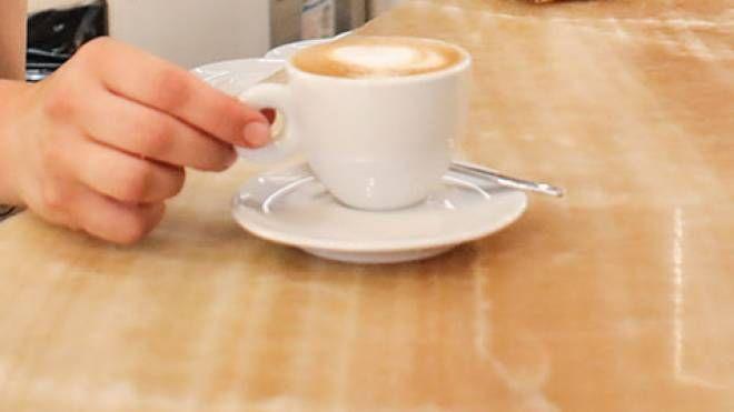 Una barista serve un cappuccino (foto d'archivio)