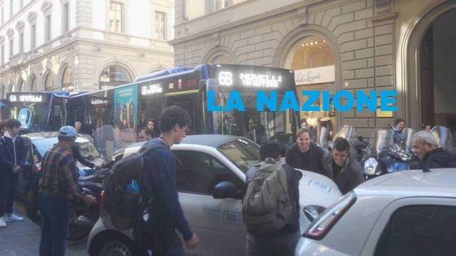 I passanti spostano l'auto che blocca il bus