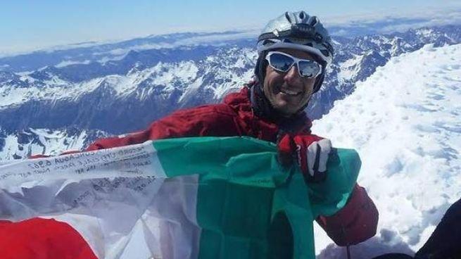 Luca Colli in cima a una vetta alpina col tricolore