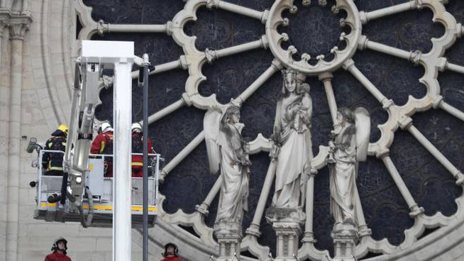 I pompieri francesi al lavoro vicino al rosone di Notre Dame (Ansa)