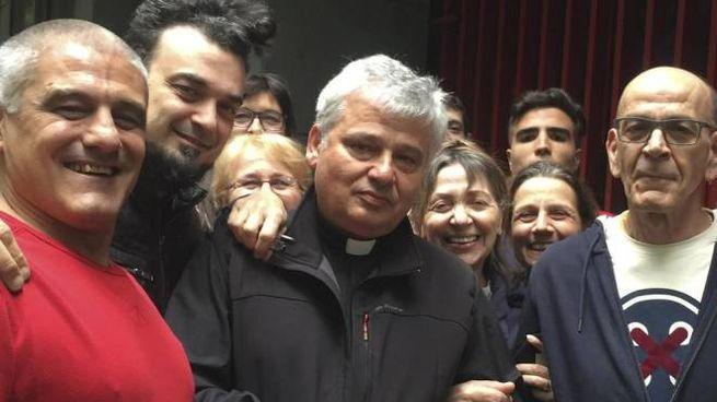 Il cardinale Konrad Krajewski con alcuni residenti nello stabile occupato (Ansa)