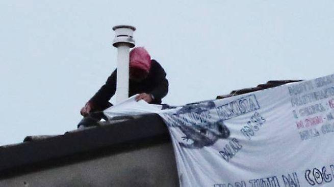 L'uomo mentre espone lo striscione sul tetto