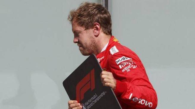Sebastian Vettel sposta il tabellone che indica il primo posto (foto Ansa)