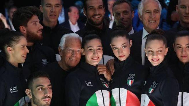 Giorgio Armani tra gli atleti alla fine della sfilata di Emporio Armani (Ansa)